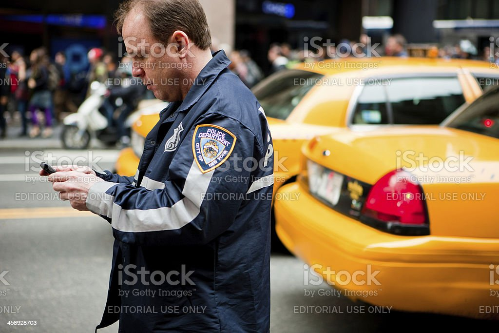 Policeman in a crowd using his mobile phone, New York stock photo