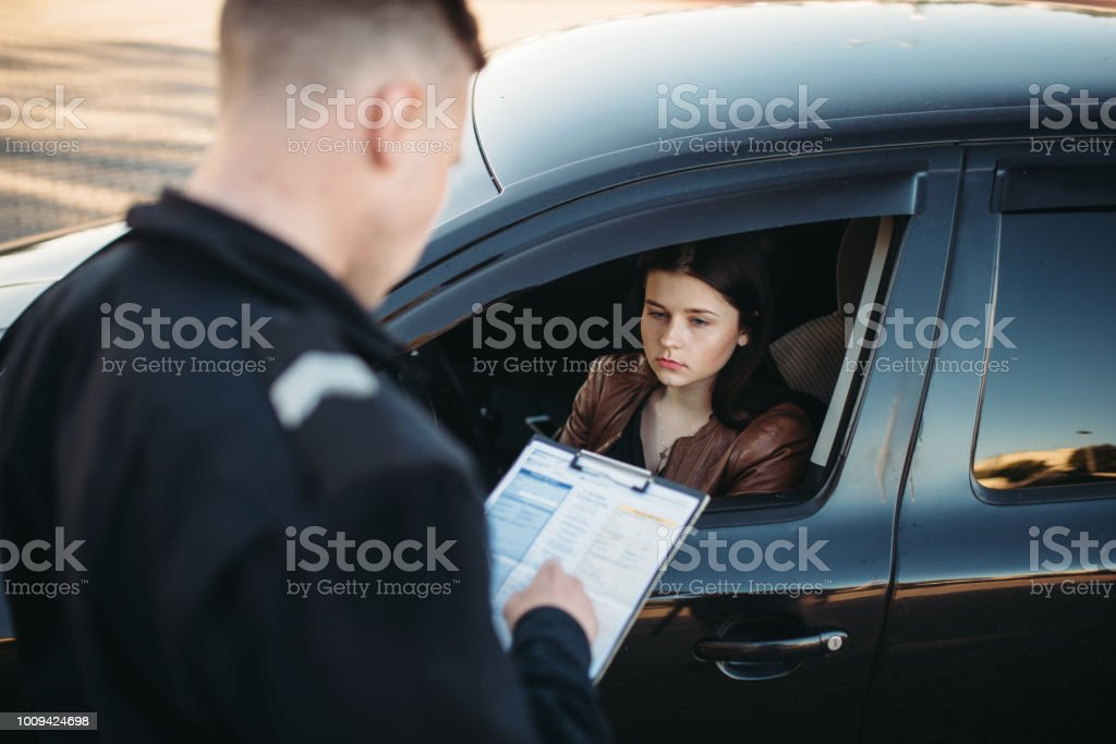 Policeman in uniform writes fine to female driver stock photo