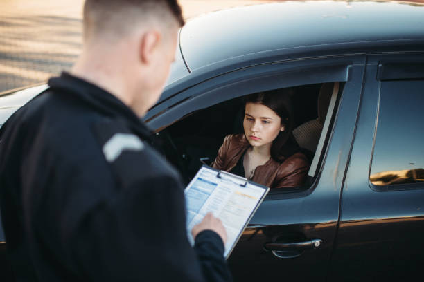 policeman in uniform writes fine to female driver - ticket stock photos and pictures