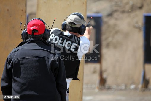Picture of a Policeman shooting handgun in a practice field.  The police officer is wearing a police kevlar vest and has earmuffs to protect him from the sound of the handgun. The shooting target is blur and visible in the background. An insctructor is in the foreground.