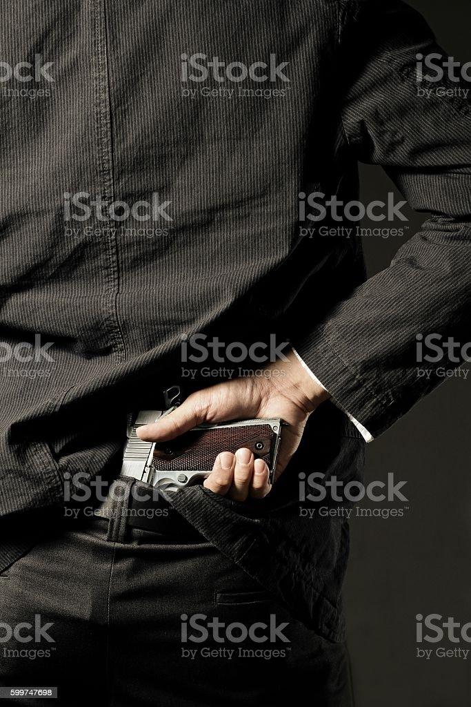 policeman or gangster concealing gun stock photo