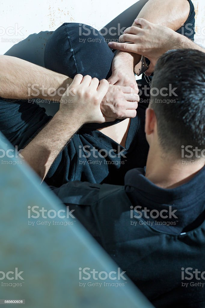 Policeman overpowering man stock photo