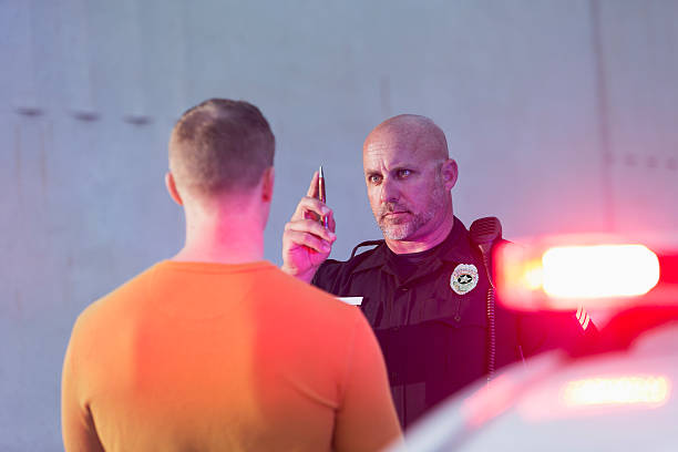 Policeman performing sobriety test on driver Police officer giving sobriety test to young man to see if he is driving under the influence of drugs or alcohol.  Police cruiser is out of focus in the foreground. arrest stock pictures, royalty-free photos & images