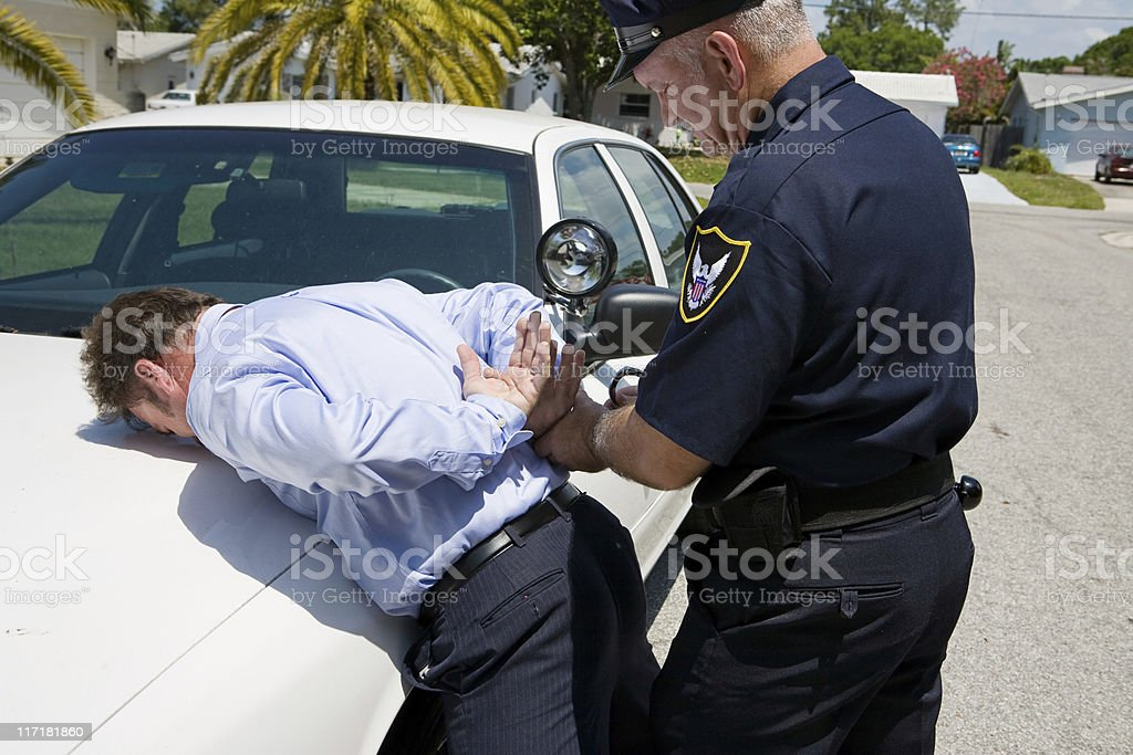 A policeman placing a man under arrest stock photo