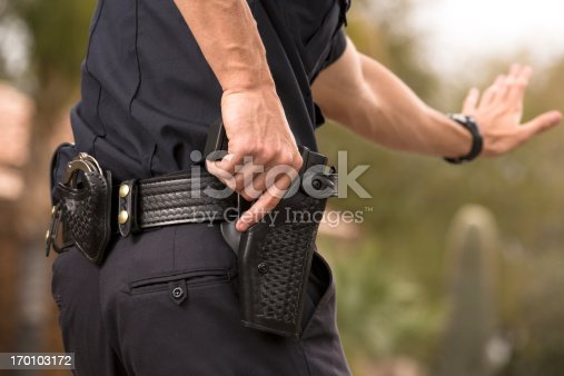Policeman preparing to draw his gun, Gold Chest Emblem Custom Ordered Generic. This stock image has a horizontal and outdoor composition.