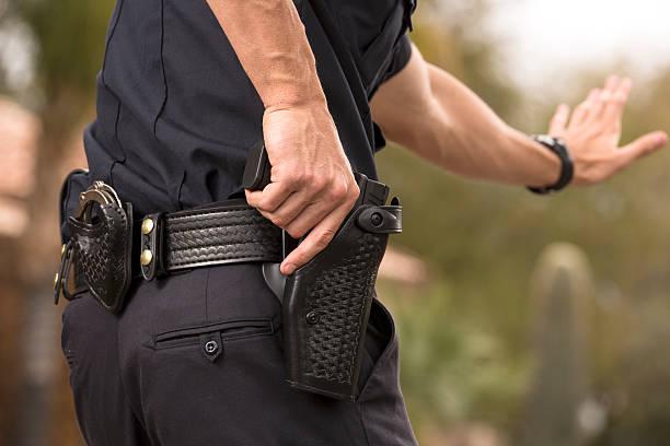 policeman preparing to draw his gun - 鎗 個照片及圖片檔