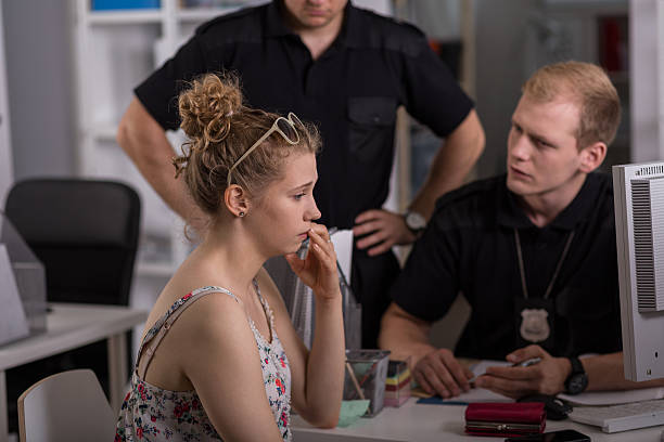 Policeman questioning woman Young policeman questioning woman at police station police interview stock pictures, royalty-free photos & images
