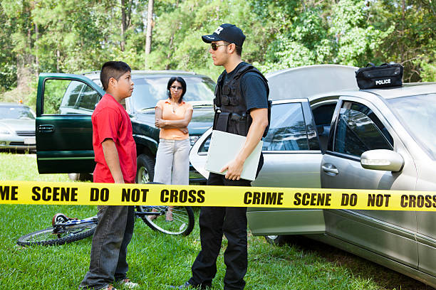 Policeman questions witnesses during vehicle accident. Policeman questions driver, witness during a vehicle accident.   police interview stock pictures, royalty-free photos & images
