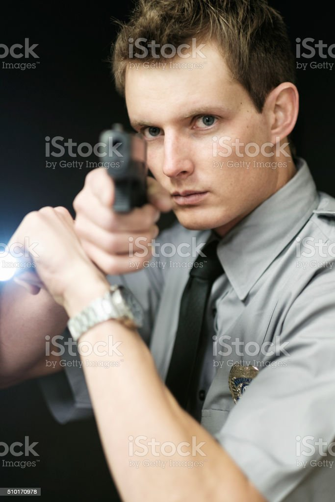 Policeman Searching a Dark Room royalty-free stock photo