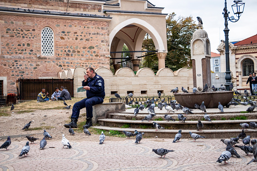 A policeman sits near fountain in disuse crowded with pigeons and talks on the radio, three foreign young men sit on the ground in the blurred background in Sofia, Bulgaria