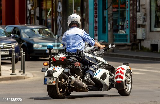 Bucharest, Romania - July 25, 2019: A policeman ride a three-wheeled motorcycle, Can-Am Spyder, in downtown Bucharest. This image is for editorial use only.