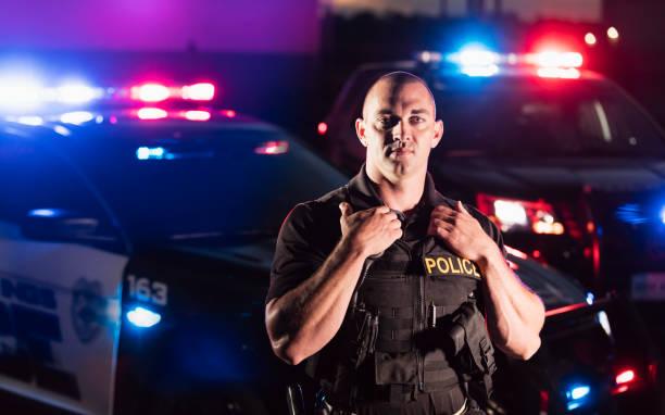 policjant ubrany w kamizelkę kuloodporną, przez samochód patrolowy - policja zdjęcia i obrazy z banku zdjęć