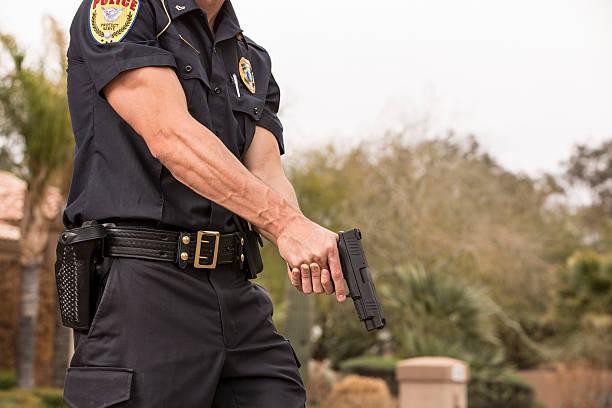 polizist mit seiner waffe gezogen, - schusswaffe stock-fotos und bilder