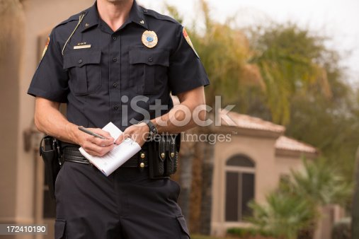 Policeman writting a ticket, Gold Chest Emblem Custom Ordered Generic. This stock image has a horizontal and outdoor composition.