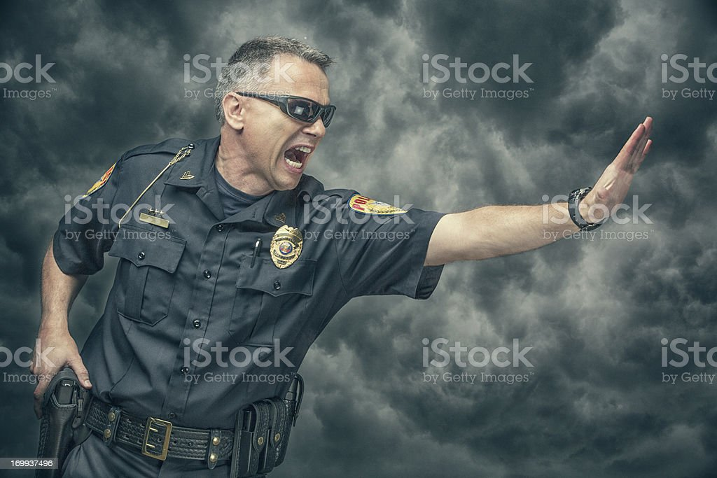 Policeman yelling and gesturing to stop stock photo