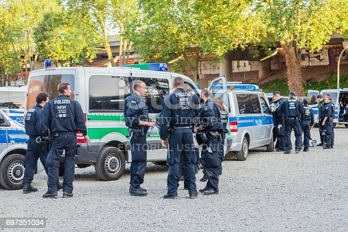 istock Policemen and policewomen in an action in front of the Cologne exhibition grounds. 697351034