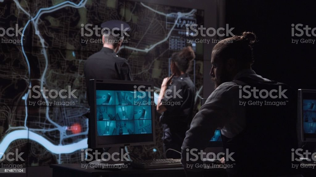 Policemen chasing gang from surveillance office stock photo