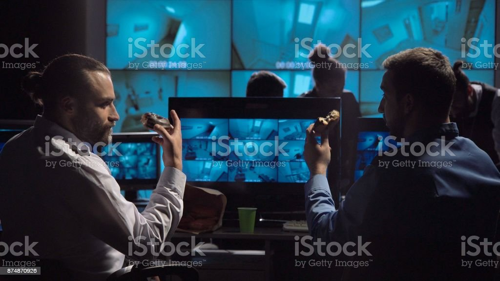 Policemen having snack at workplace stock photo