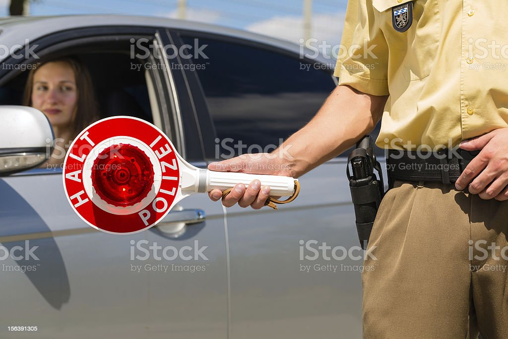 Policemen or cop stop car holding a sign that says halt stock photo