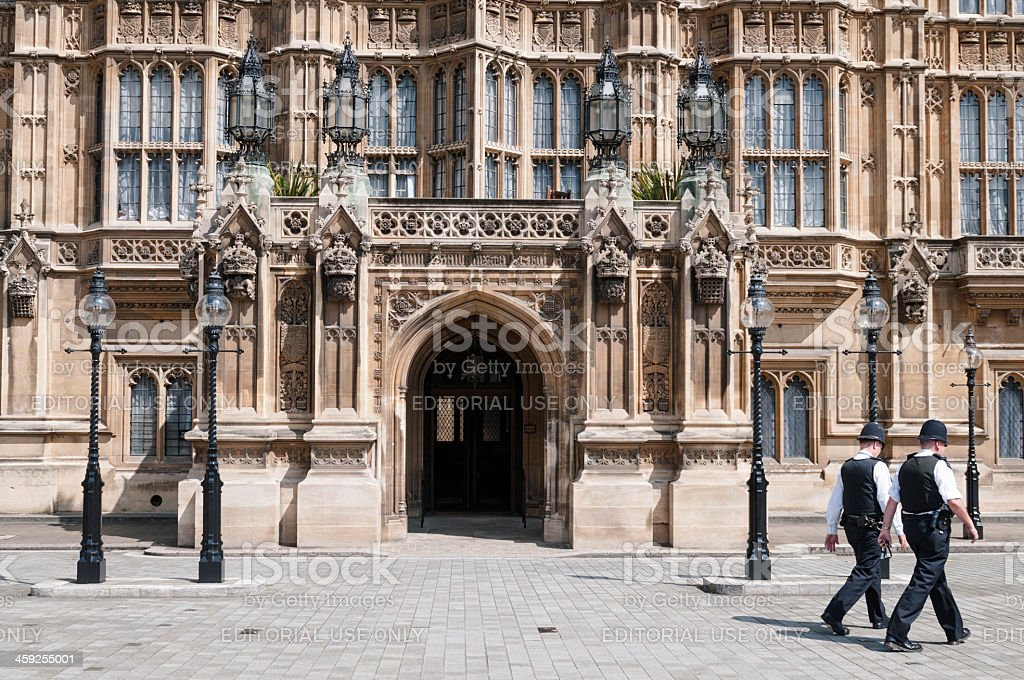 Policemen Passing Houses of Parliament in London stock photo