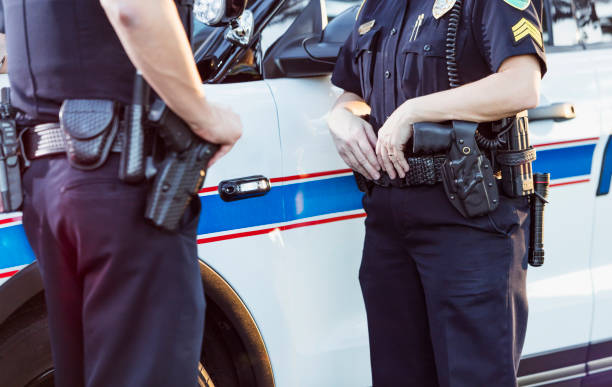 Policewoman and partner next to squad car Cropped view of police officers standing beside a squad car having a conversation. The focus is on the policewoman whose hands are resting on her gun belt. police meeting stock pictures, royalty-free photos & images