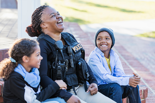 Community policing - a female police officer is conversing with a boy and his sister, sitting side by side on steps outside a building, laughing. The policewoman is African-American, in her 40s. The children are 8 and 7 years old, mixed race African-American and Caucasian.