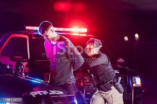 istock Policewoman putting handcuffs on suspect 1199110721