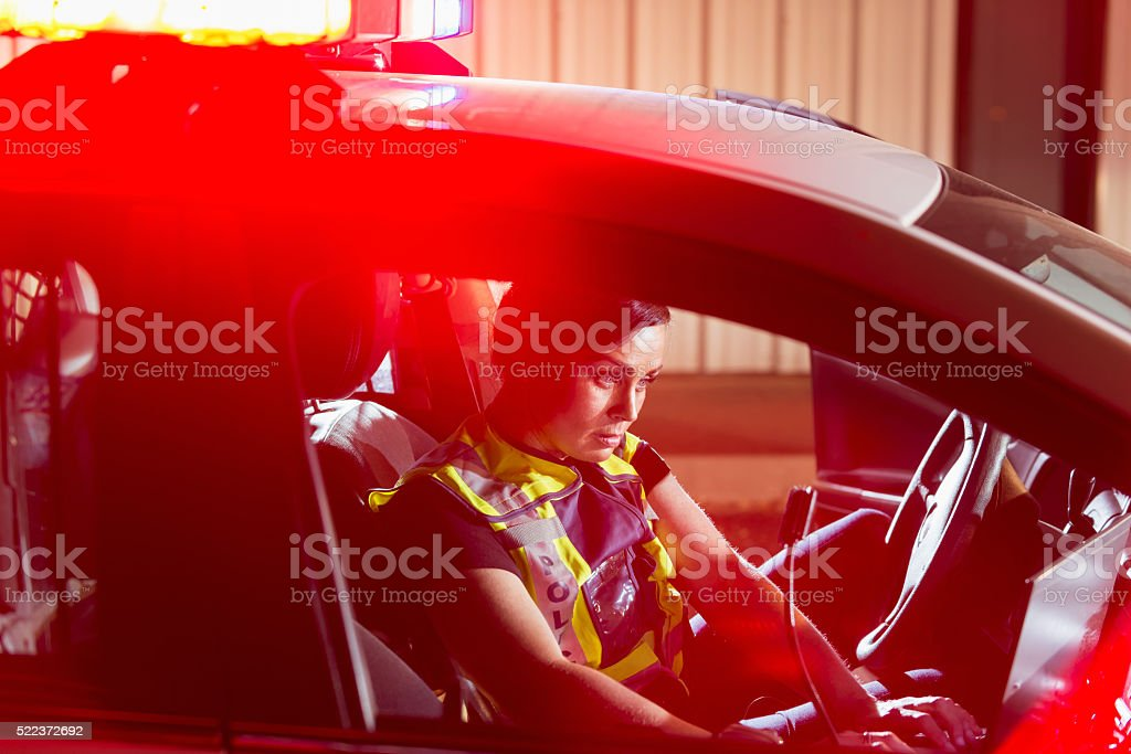 Policewoman sitting in patrol car using computer stock photo