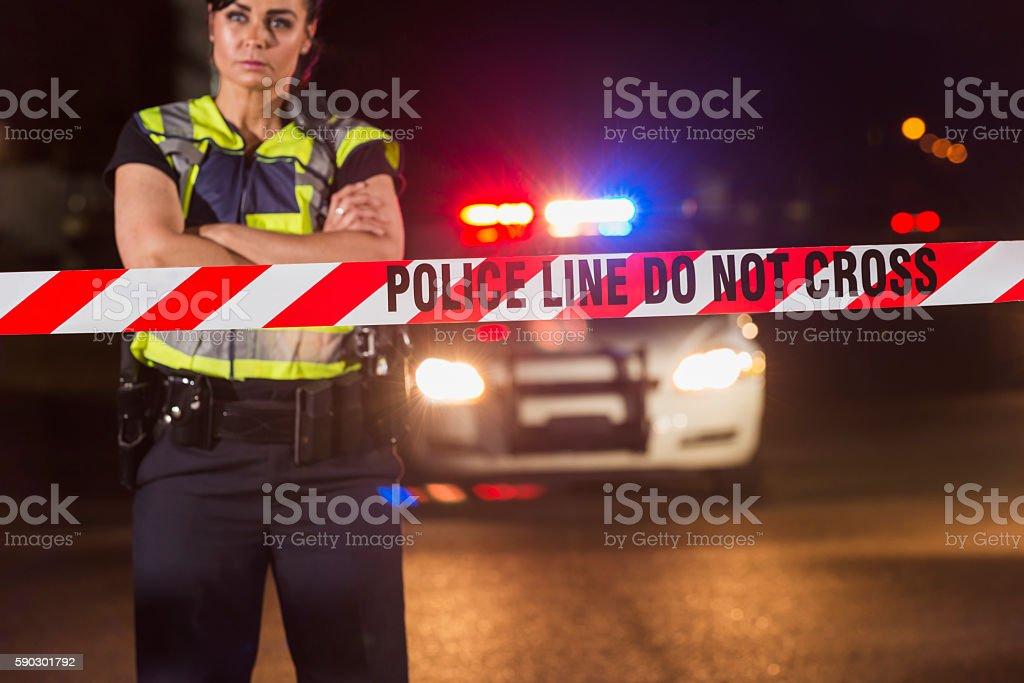 Policewoman standing behind crime scene tape royaltyfri bildbanksbilder