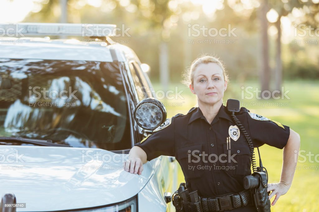Policewoman standing beside police squad car stock photo