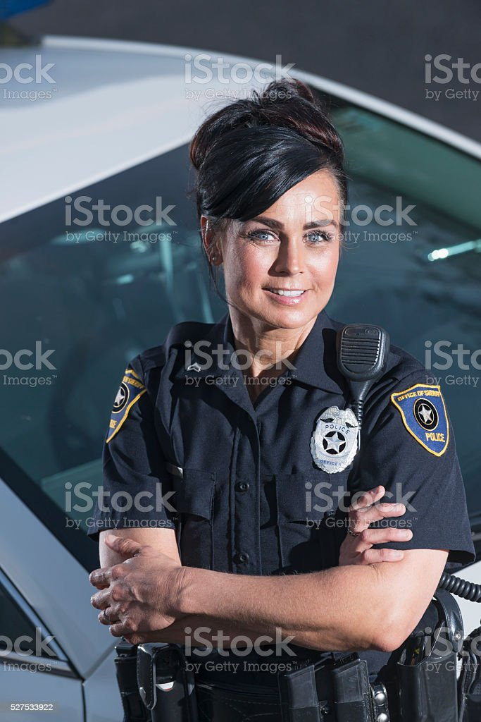 Policewoman standing next to police car, arms crossed stock photo