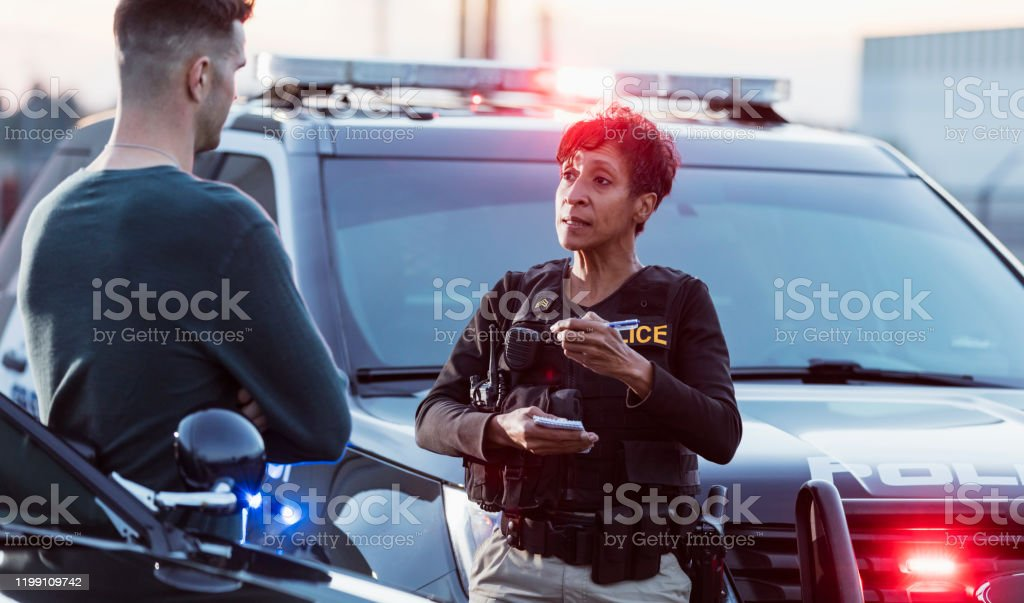 Policewoman taking a statement from young man A policewoman taking a statement from a civilian outside her patrol car. The officer is a mature African-American woman in her 40s. She is talking with a young man in his 20s. 25-29 Years Stock Photo