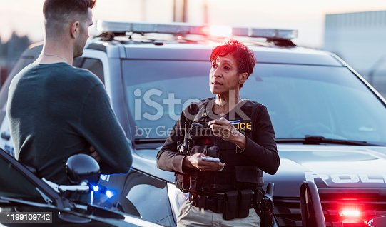 A policewoman taking a statement from a civilian outside her patrol car. The officer is a mature African-American woman in her 40s. She is talking with a young man in his 20s.