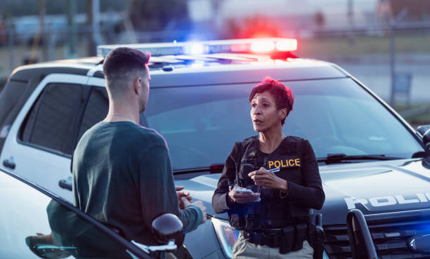 Policewoman taking a statement from young man stock photo