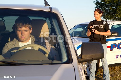 A police woman writes a man a ticket (focus police)