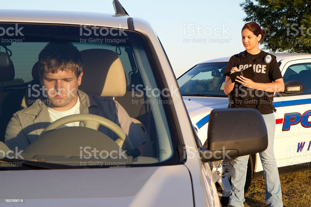 Policewoman writing man ticket (focus police) stock photo