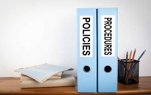Policies and Procedures binders in the office. Stationery on a wooden shelf