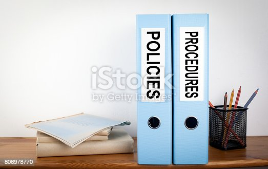 464906632 istock photo Policies and Procedures binders in the office. Stationery on a wooden shelf 806978770