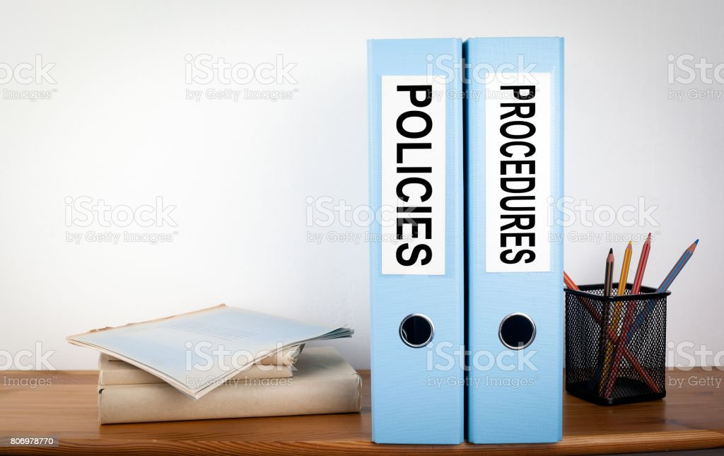Policies and Procedures binders in the office. Stationery on a wooden shelf stock photo
