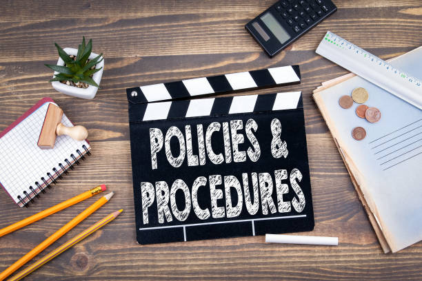 Policies and Procedures. movie clapper on a wooden desk stock photo