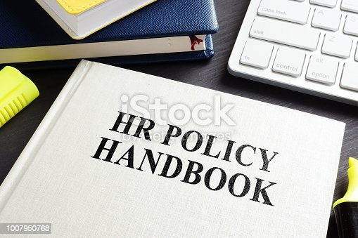 HR policy handbook on an office desk.