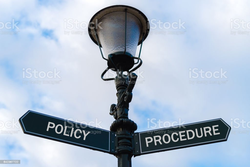 Policy versus Procedure directional signs on guidepost stock photo