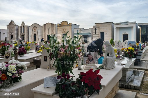 Polignano a Mare, Italy - December 25, 2016: Detail view of the cemetery in Polignano a Mare on Christmas day. On the right a lady with a blue bucket apparently cleaning a grave.