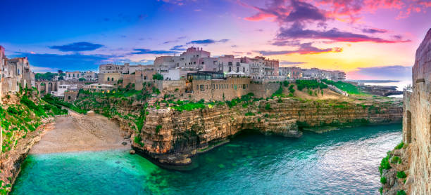 Polignano a Mare, Puglia, Italy: Sunset at Cala Paura gulf with Bastione di Santo Stefano and Lama Monachile beach stock photo