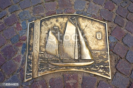 Poland, Gdansk, May 25, 2019: Gdansk in Poland and its embankment - port and marina with modern and old ships, motor and sailing, expensive and cheap. Copper plate on the road in the port.