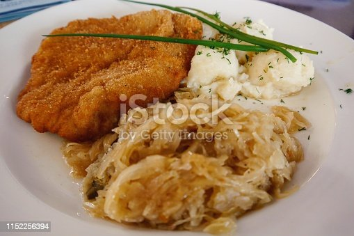 A traditional plate of Polish Kotlet schabowy, served with pickled cabbage and puréed potatoes on a white porcelain plate.