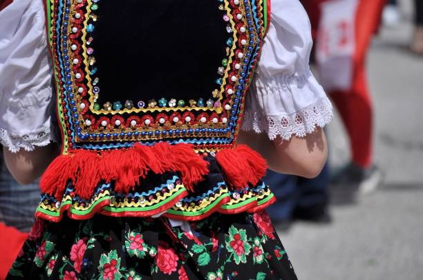Polish traditional folk costume. Polish heritage. Beautiful, colorful, handmade folk costume. Vest with beads, sequins, ribbons, red fringes and flowery skirt. polish culture stock pictures, royalty-free photos & images