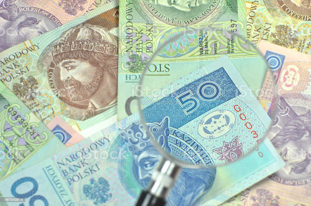 polish zloty banknotes under magnifying glass stock photo