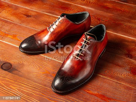 Polished leather fashion shoes on a wooden background close up, side view