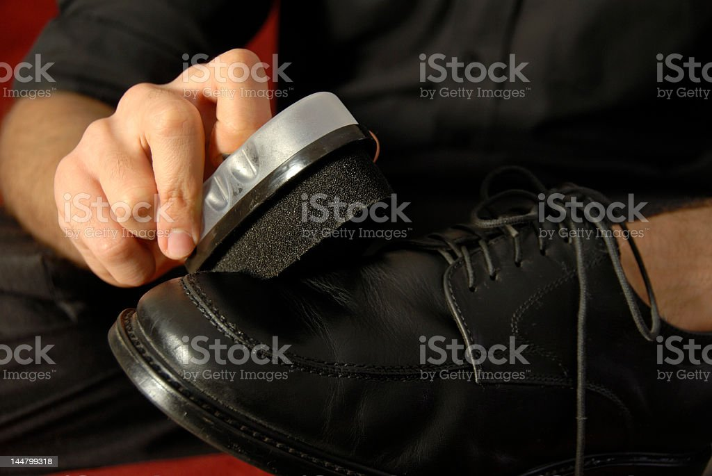 Polishing a black leather shoe stock photo